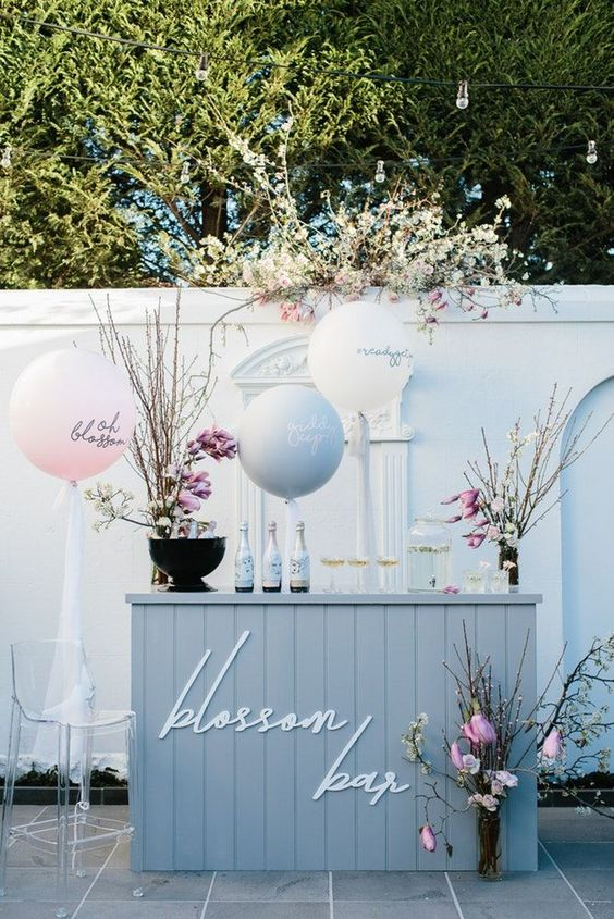 a spring blossom bar with blooming branches, cute balloons and cool drinks for a modern spring bridal shower