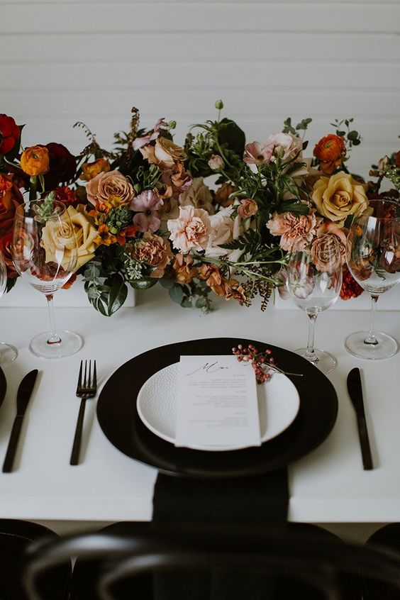 a stylish modern fall wedding tablescape with a black charger, black cutlery, lovely blush, peachy, rust and yellow blooms and greenery