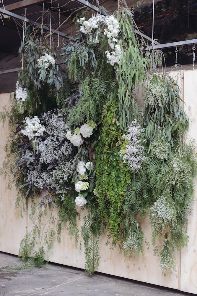 a wedding backdrop with lots of greenery and overgrown blooms hanging down is a gorgeous solution for a ceremony or photo booth
