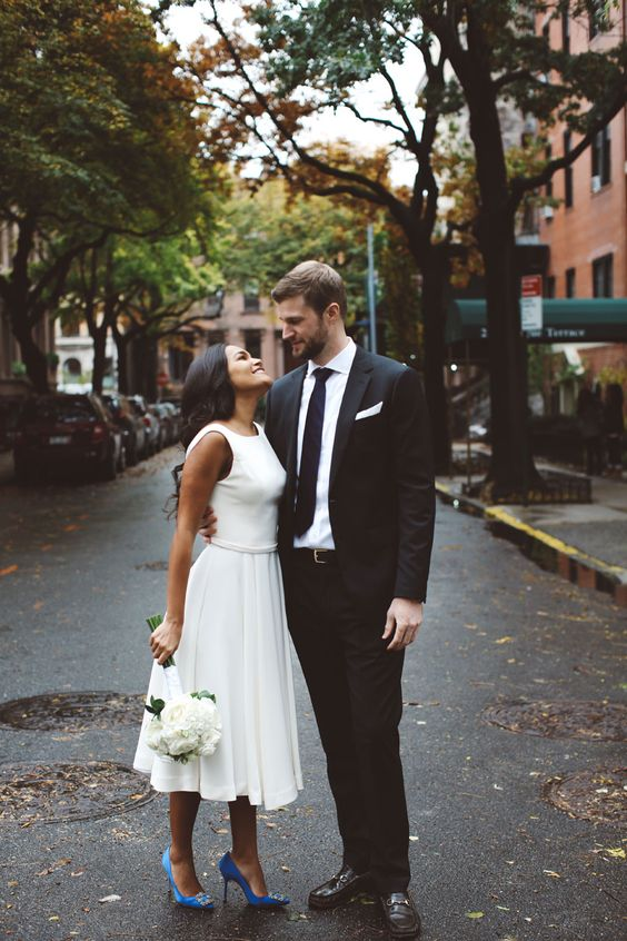 a casual sleeveless midi wedding dress with a plain bodice, a pleated skirt, blue heels for a chic and pretty bridal look