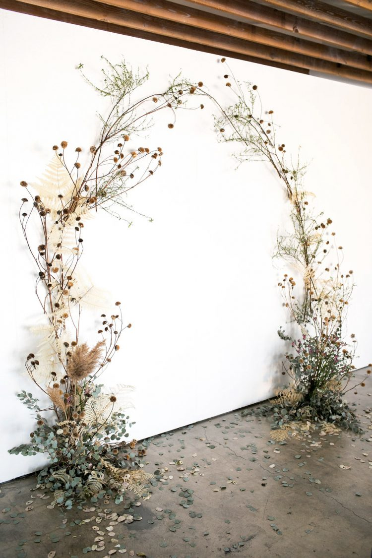 a pretty boho wedding arch of greenery, dried overgrown blooms and leaves is a very cool idea for a fall wedding