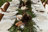 24 a pretty rustic wedding tablescape with evergreens, pinecones, fabric and natural pumpkins, candles and white porcelain