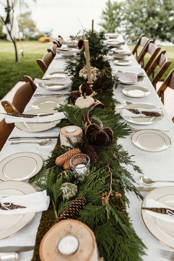 a pretty rustic wedding tablescape with evergreens, pinecones, fabric and natural pumpkins, candles and white porcelain