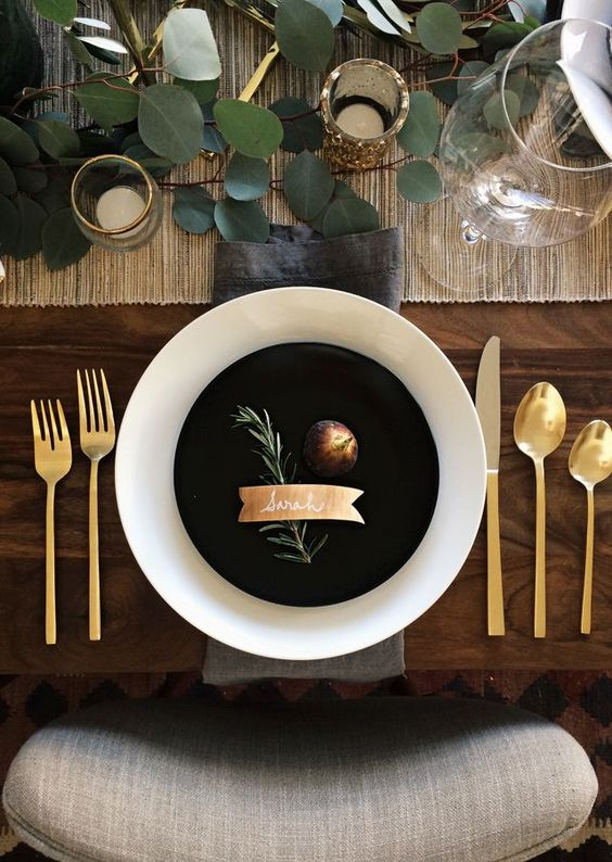 a stylish modern fall wedding table setting with a woven table runner, eucaly[tus, candles in gold candleholders, black and white plates and gold cutlery
