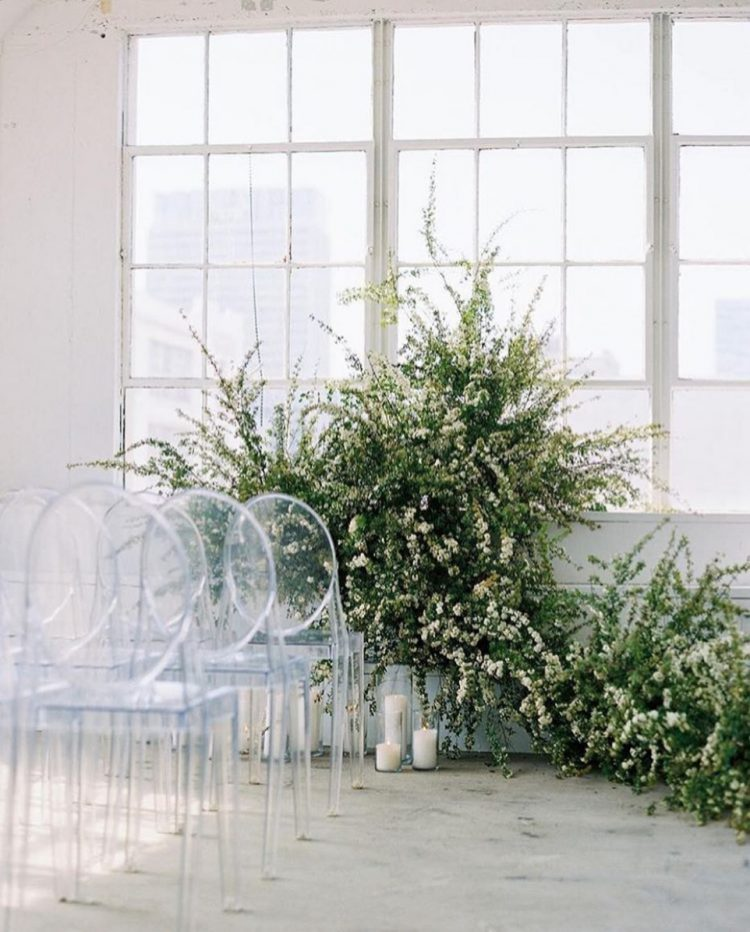 a lovely modern wedding ceremony space with lots of greenery and white blooms forming a wedding altar looks amazingly inspiring