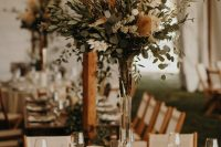 25 a neutral and chic boho backyard wedding reception space with pretty greenery and pampas grass centerpieces, candles and neutral linens is chic
