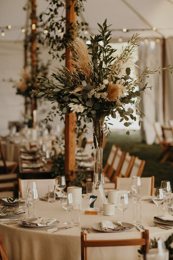 a neutral and chic boho backyard wedding reception space with pretty greenery and pampas grass centerpieces, candles and neutral linens is chic
