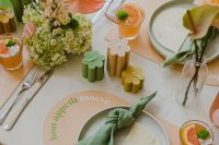25 a pretty modern pastel bridal shower table with green and orange blooms, with flower-shaped candles, pastel placemats and napkins