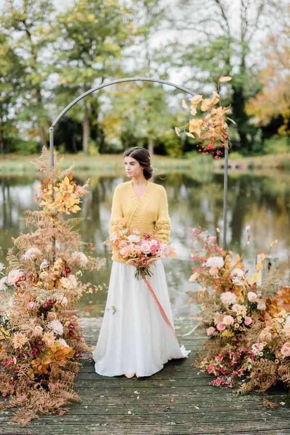 a sophisticated modern wedding arch with bright fall leaves, blush, white and mustard blooms and a gorgeous lake view is wow