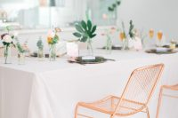 26 a modern tropical bridal shower table with pink and blush blooms, statement tropical elaves, copper chargers and black plates