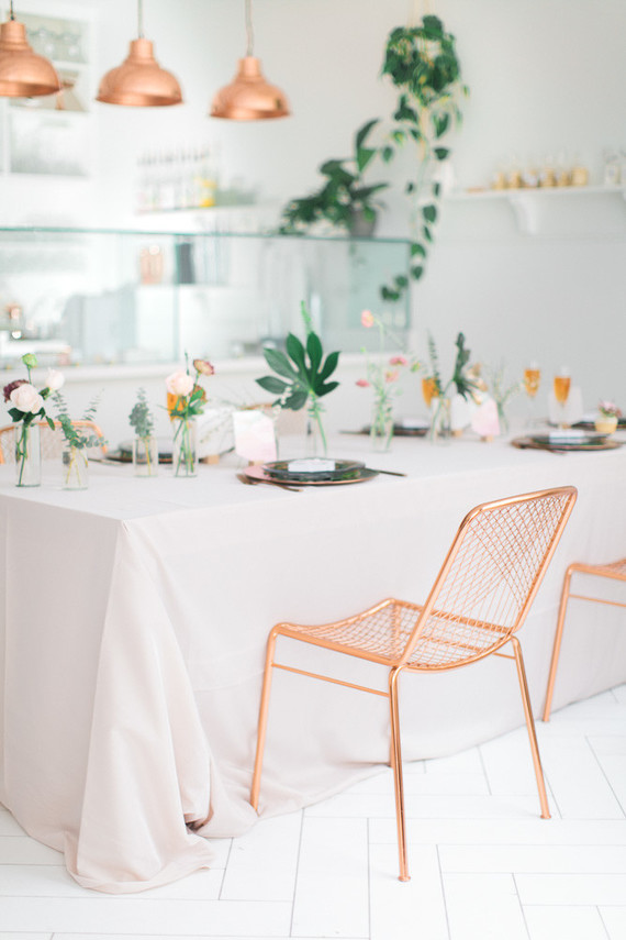 a modern tropical bridal shower table with pink and blush blooms, statement tropical elaves, copper chargers and black plates