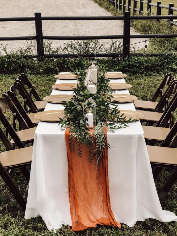 a simple modern fall wedding tablescape with gilded chargers, a greenery runner, candles and a rust-colored table runner