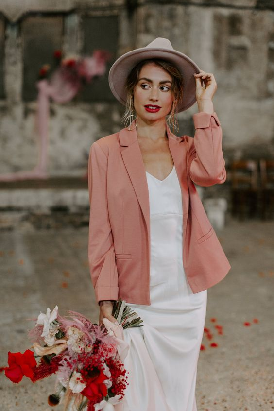 a plain silk slip wedding dress, a pink blazer and a hat for a creative yet casual bridal look with a touch of color