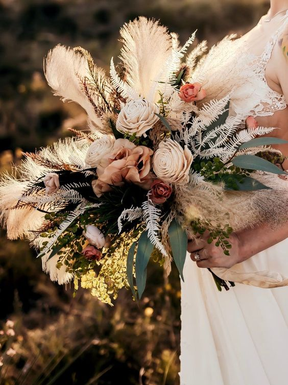 a refined boho fall wedding bouquet with blush blooms, pampas grass, greenery, dried hydrangeas and other textural elements