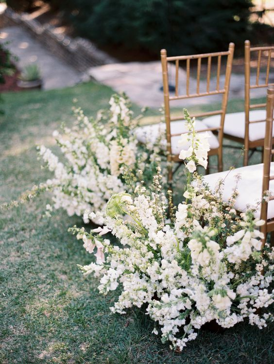 overgrown flowers lining up the wedding aisle look chic, beautiful and out-of-the-box and make the space more romantic