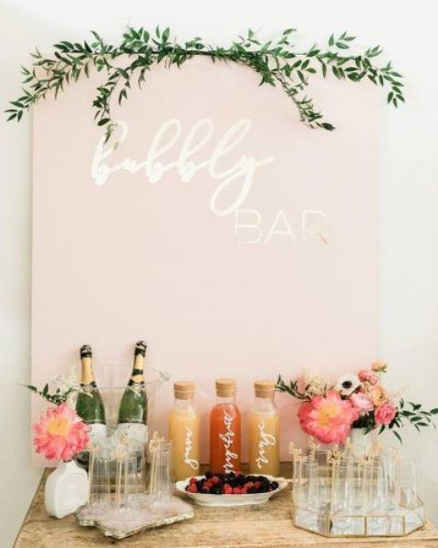 a glam modern bridal shower bubbly bar with a pink sign, greenery, pink floral arrangements and some drinks and glasses