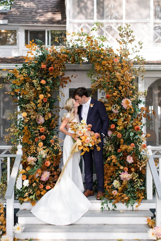 a refined and cool modern fall wedding arch composed of bold rust, yellow, mustard blooms and greenery and bright fall leaves