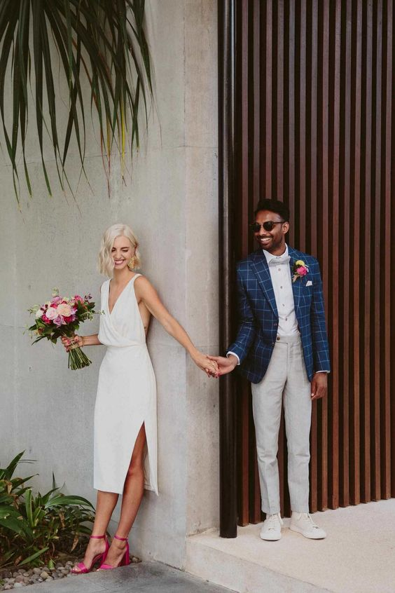 a simple and cool white midi wedding dress with a deep neckline, thick straps, a side slit, pink ankle strap shoes is wow