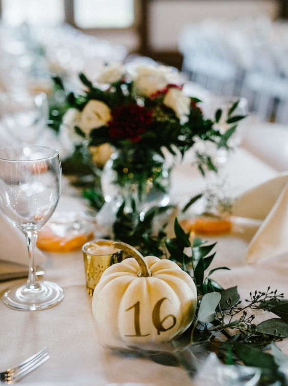 elegant rustic fall wedding table decor with a greenery runner, a white pumpkin with a number, gilded candleholders and chic touches