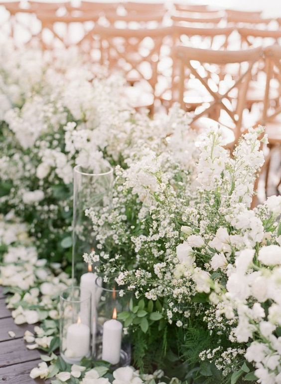 overgrown white wedding blooms with greenery, petals and candles lining up the aisle look gorgeous and chic