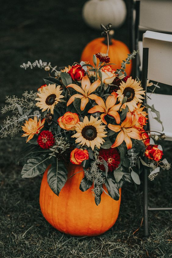 a cool rustic fall wedding decoration of a bold pumpkin, greenery, burgundy, deep red and orange blooms is a lovely idea for a wedding aisle or table