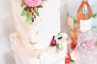 29 a gorgeous modern bridal shower cake with pink watercolor, gold leaf, neutral and bold blooms plus green leaves