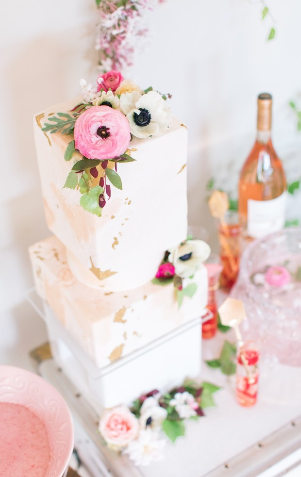 a gorgeous modern bridal shower cake with pink watercolor, gold leaf, neutral and bold blooms plus green leaves