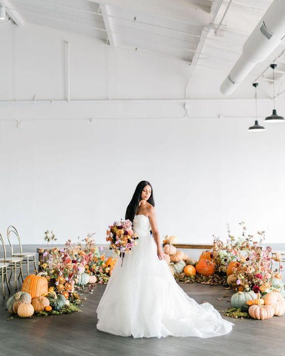 a modern rustic fall wedding altar with pumpkins, greenery and bold fall leaves is beautiful idea to steal