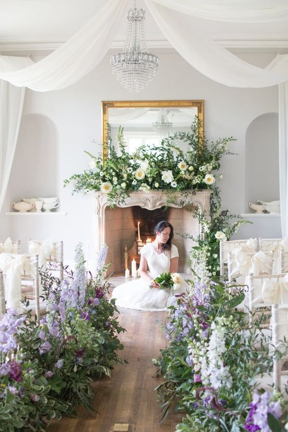 a refined wedding ceremony space with a chic fireplace, lots of white, peachy and purple overgrown blooms and a large mirror