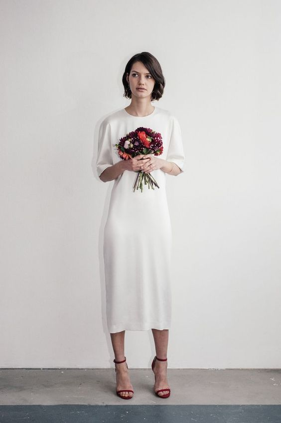 a simple plain silk midi wedding dress with a high neckline, short sleeves, burgundy shoes are a cool idea for a casual bride