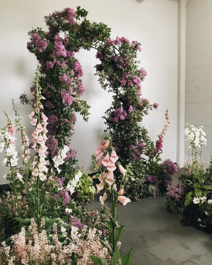 a garden-like wedding ceremony space is done with greenery, blush, pink and white overgrown blooms, an arch covered with greenery and lilac