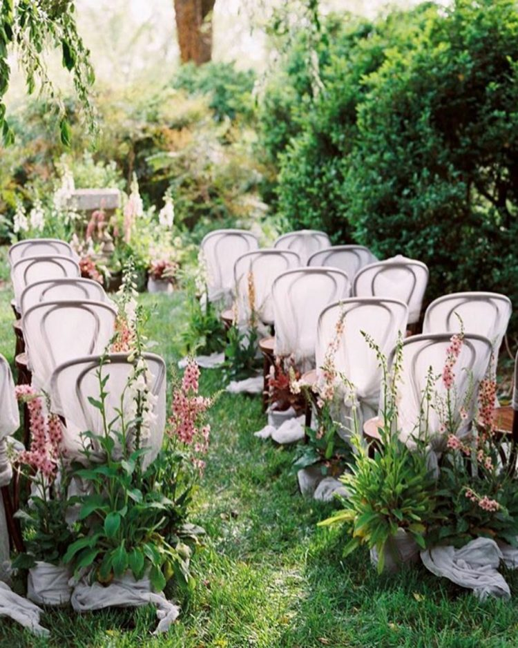 a beautiful and a bit wild wedding ceremony space on a lawn, with overgrown blooms lining up the aisle and an altar of the same blooms