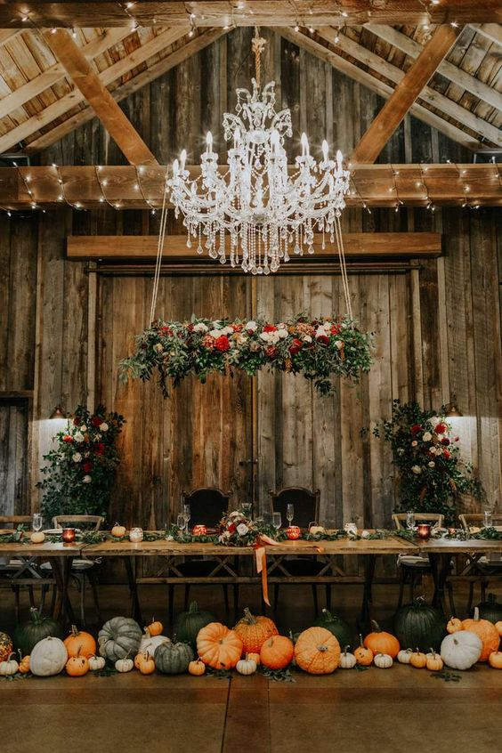 a fantastic fall rustic wedding reception with lots of pumpkins on the floor, bold blooms and neutral ones, greenery and colorful ribbons