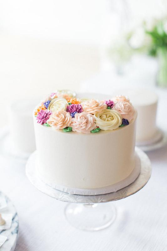 a modern bridal shower cake covered with white buttercream and topped with colorful sugar bloooms is a cute desserts that your gals will like