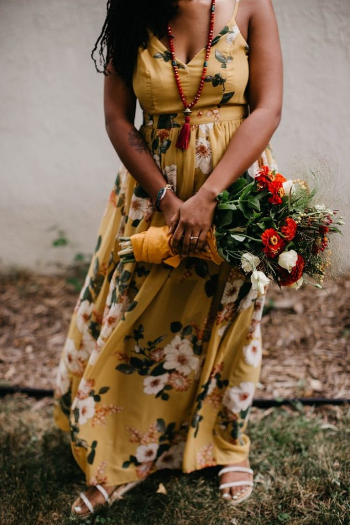 a yellow floral A-line maxi dress, a red necklace with a tassel and strappy sandals for a chic and relaxed summer bridal look