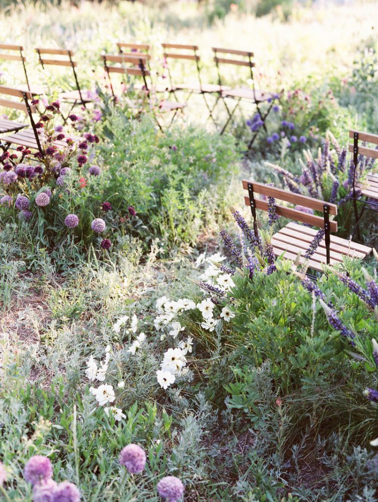 a beautiful and wild blooming space with lots of purple, fuchsia, white, pink blooms and greenery turned into a wedding ceremony space