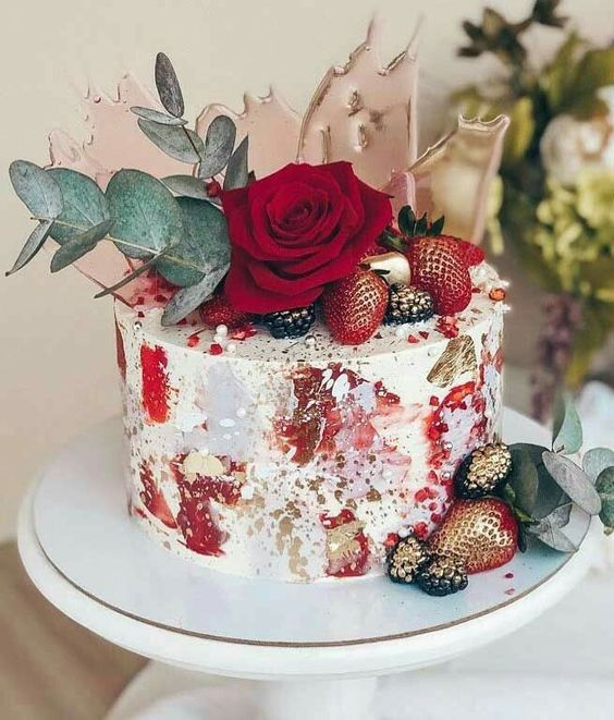 a gorgeous modern fall wedding cake with bright abstract brushstrokes, gold splashes, a red rose, blackberries, strawberries and pink shards