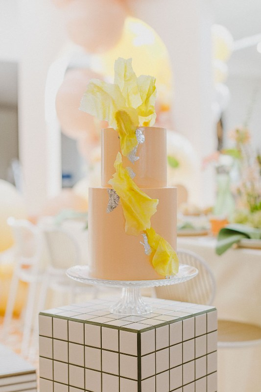 a modern bridal shower cake in pastel orange, with yellow sugar petals and silver leaf is an out of the box idea
