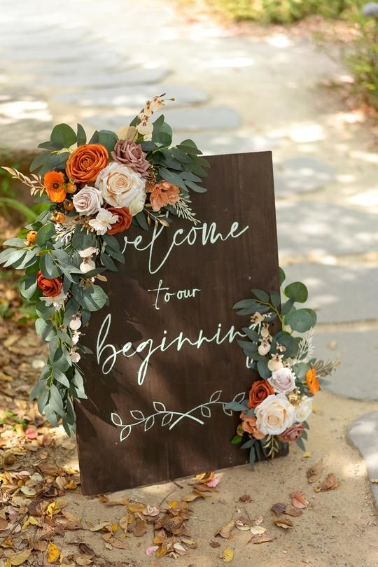 a rustic fall wedding sign with greenery, white, rust, orange and blush blooms and calligraphy is a stylish and cool idea