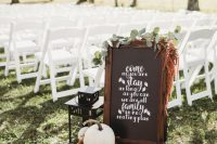 32 simple backyard fall wedding decor with a chalkbaord sign, greenery, dried blooms, pumpkins and a candle lantern