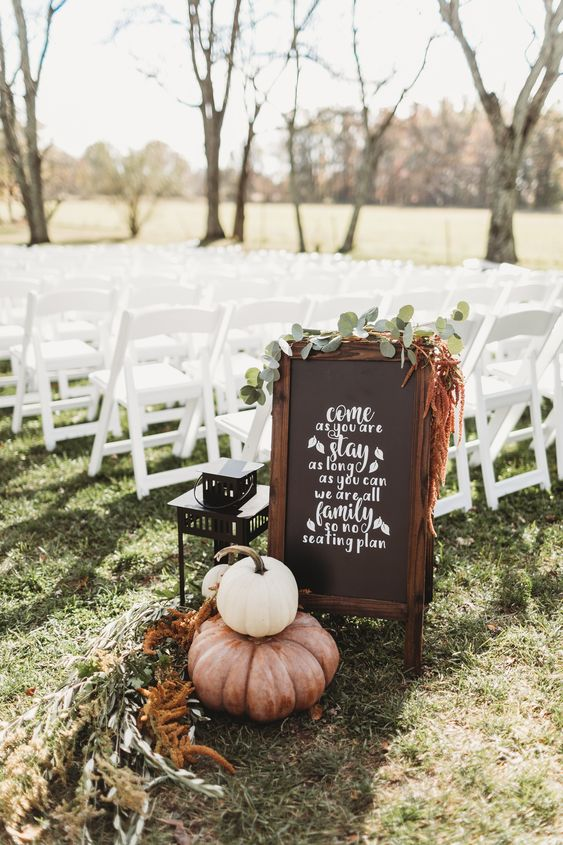 simple backyard fall wedding decor with a chalkbaord sign, greenery, dried blooms, pumpkins and a candle lantern