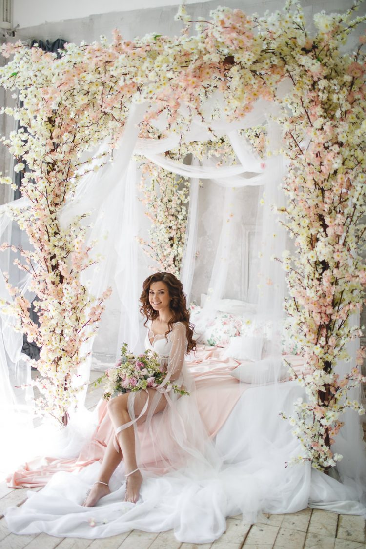 a canopy bed styled for bridal preparations with lots of pink and vanilla-colored silk flowers is a creative and romantic idea
