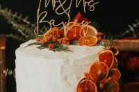 33 a gorgeous fall wedding cake with dried citrus slices, greenery, berries and a cool calligraphy cake topper
