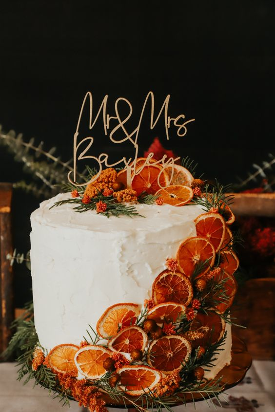 a gorgeous fall wedding cake with dried citrus slices, greenery, berries and a cool calligraphy cake topper