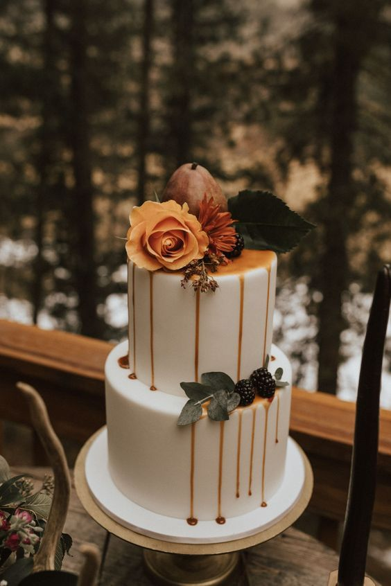 a gorgeous modern fall wedding cake with caramel drip, a pear and blackberries, an orange rose and leaves is amazing