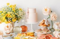33 a modern pastel bridal shower dessert table with bold blooms and pastel ones, with desserts, appetizers and a pastel pink wedding cake