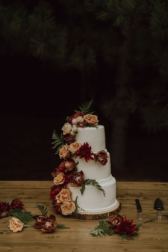 a lovely and chic white wedding cake decorated with rust and burgundy blooms and fern is a pretty solution for a backyard fall wedding