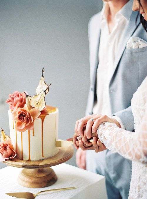 a modern fall wedding cake with caramel drip, pear slices, pink blooms is a gorgeous idea for the season