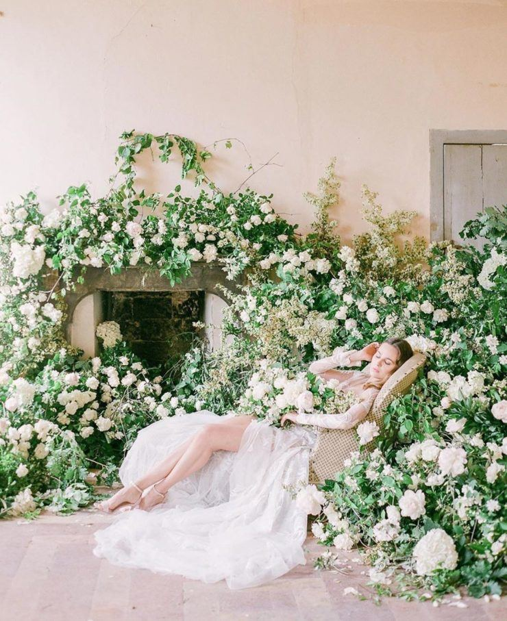 a wedding ceremony space with overgrown white peonies and greenery covering the space around the fireplace is lovely