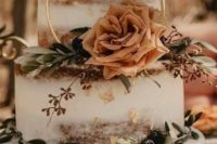 35 a naked fall backyard wedding cake with eucalyptus, a rust-colored rose and a gold ring plus dried blooms is chic